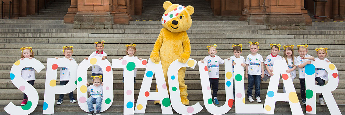 Children with Pudsey ears holding letters that spell out 'Spotacular' with Pudsey the bear in the middle on concrete steps