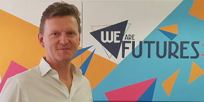 Mark Fawcett in front of We are Futures wall art