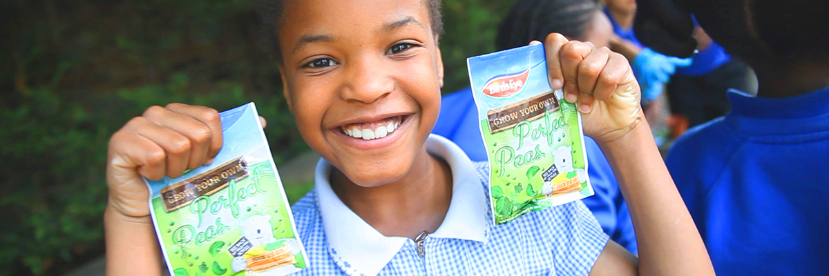 young girl in school dress smiling and holding up two packets of birds eye pea seeds