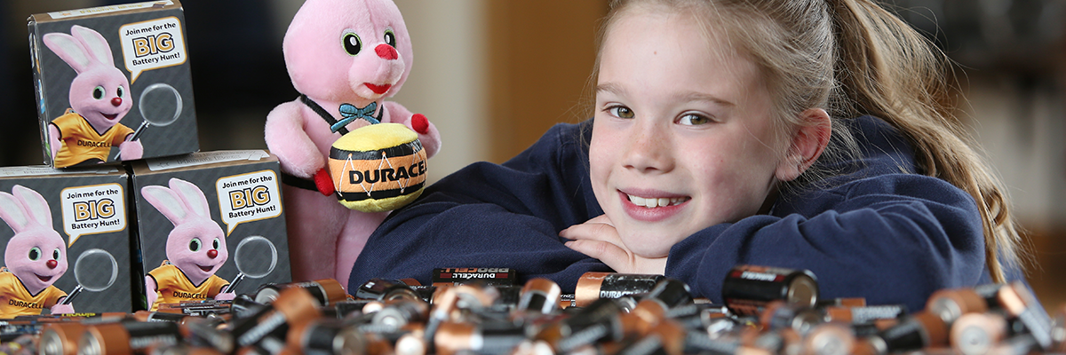 Young school girl with head on hands behind batteries on a table with big battery hunt boxes and duracell bunny
