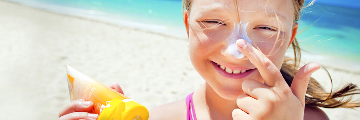 young girl on the beach in the sun putting suncream on her nose and smiling