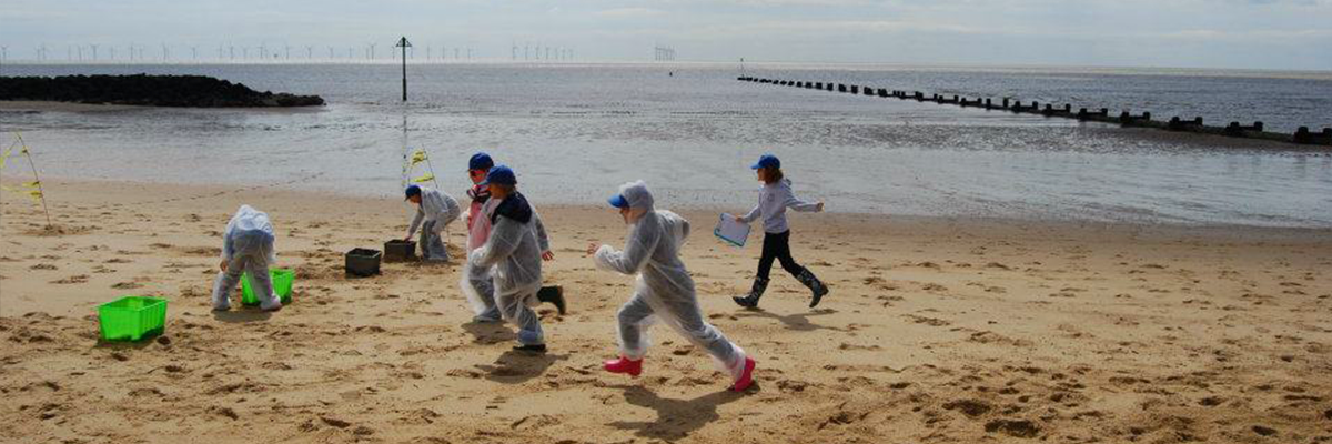 children in overalls running on the beach