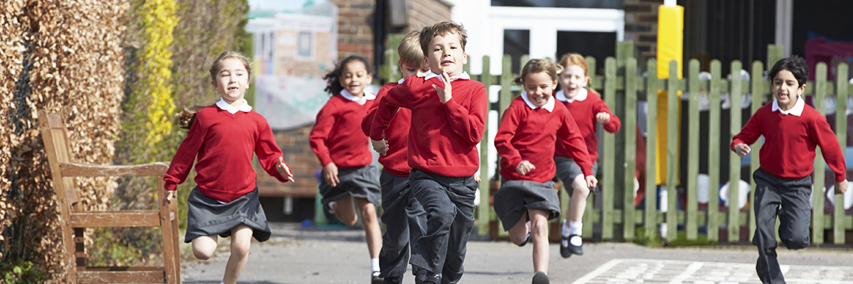 school children outside running and dressed in red