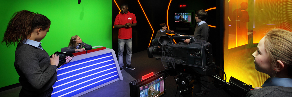 school children in sky skills studio operating camera and filming school child at news desk