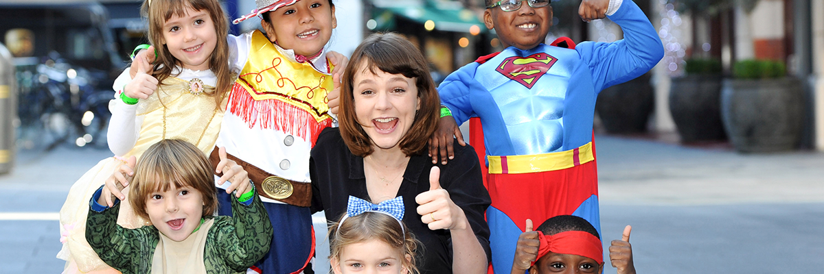 carey mulligan surrounded by school children in fancy dress including superman outfit and cowboy outfit outside