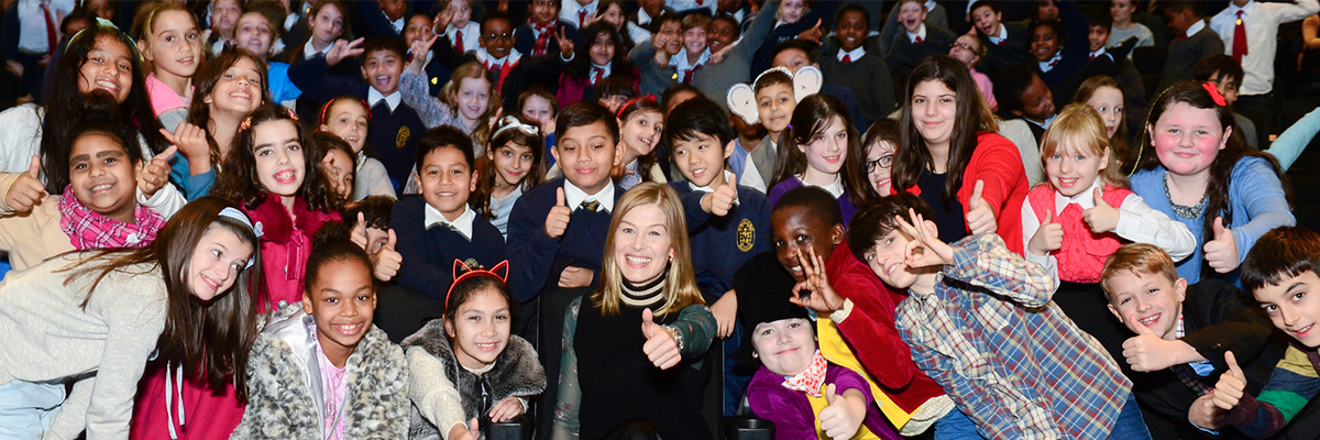 rosamund pike with thumbs up in the middle of school children in cinema