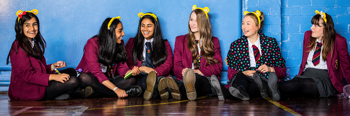 young female students in uniform sitting in front of wall with pudsey ears