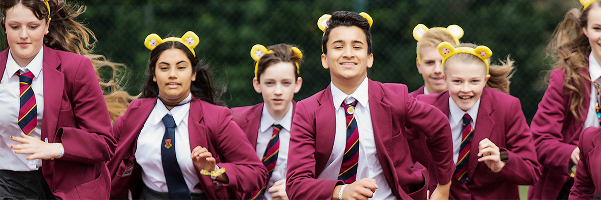 School children in uniform wearing Pudsey ears running outside