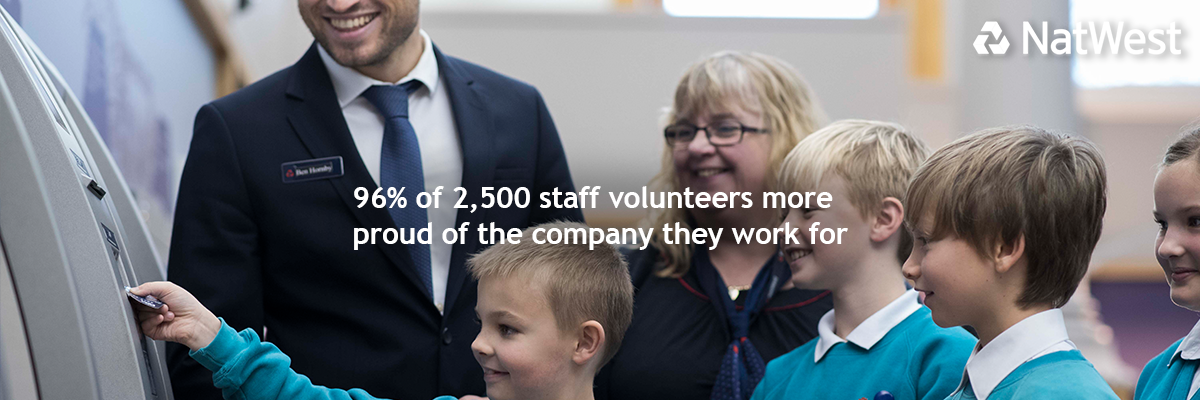 Children in school uniform putting bank card in cash machine with bank employees in a bank and '96% of 2,500 staff volunteers more proud of the company they work for' stat