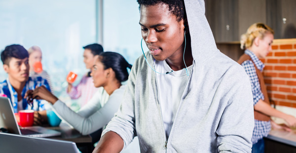 young adult in hoodie with green headphones looking at a laptop in a cafe