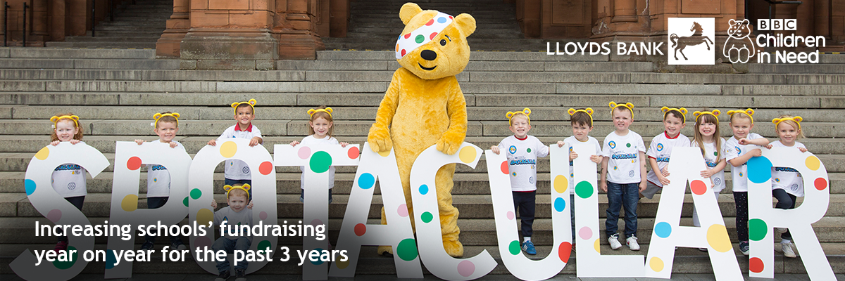 Children with Pudsey ears holding letters that spell out 'Spotacular' with Pudsey the bear in the middle on concrete steps and 'increasing school's fundraising year on year for the past 3 years' stat