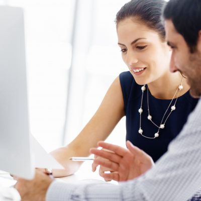 Man and woman in modern office looking at piece of paper