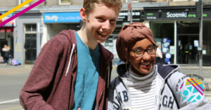 Two young people smiling in the sun with the year of young people logo