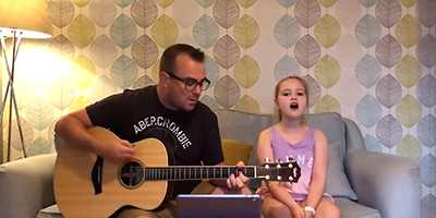 Father playing guitar and daughter, Mayana, singing on a sofa for her British Glass competition winning entry