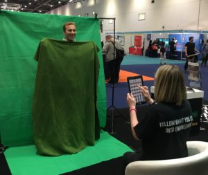 Ben Ryall posing in front of a green screen holding a green sheet to cover his body and a member of world skills live uk staff taking pictures on an iPad