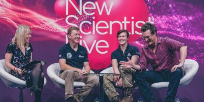 Astronaut Time Peake and Explorer Nics Wetherill being interviewed by two presenters with New Scientist Live logo in the background